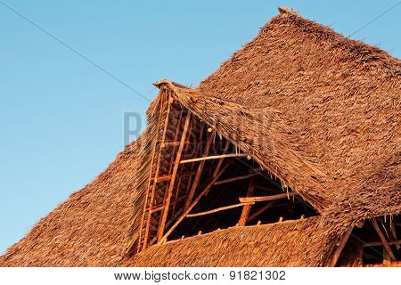 Rustic African thatched roof against a blue sky with clouds