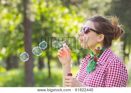 Cheerful Beautiful Brunette Girl In Glasses Blowing Soap Bubbles Outdoor