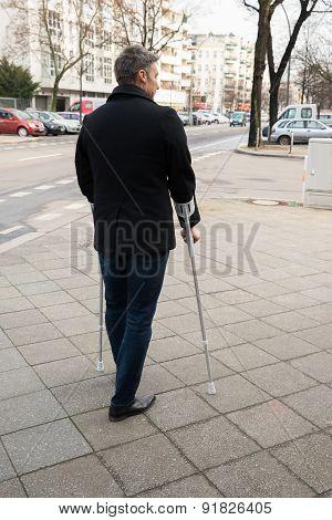 Man Walking On Street Using Crutches