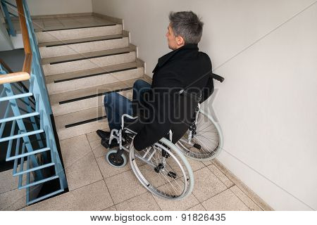 Disabled Man On Wheelchair In Front Of Staircase