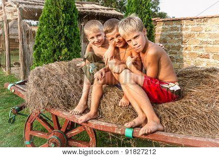 boys sitting on a hay bale