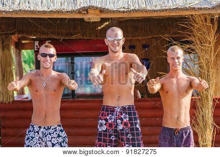 Joyful team of friends having fun at the beach in cafe