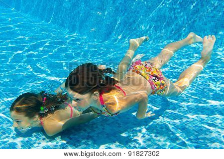 Happy active kids swim in pool and play underwater, girls diving and having fun
