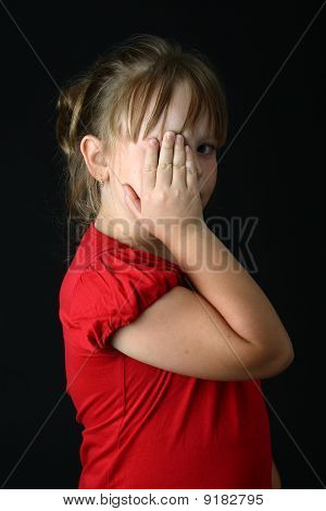 Small girl covering one eye with her hand on black