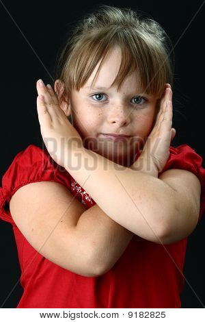Small girl making X sign with her arms on black