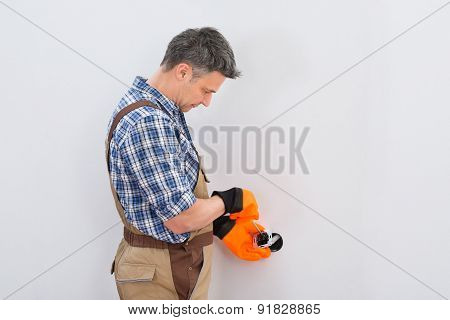 Technician Fixing Socket On Wall