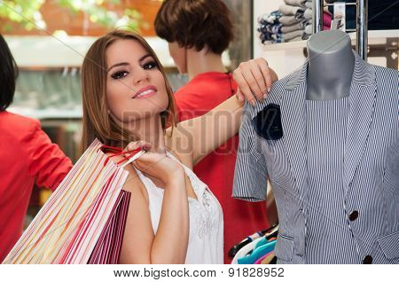 Teenage girl leaning on a doll in a boutique