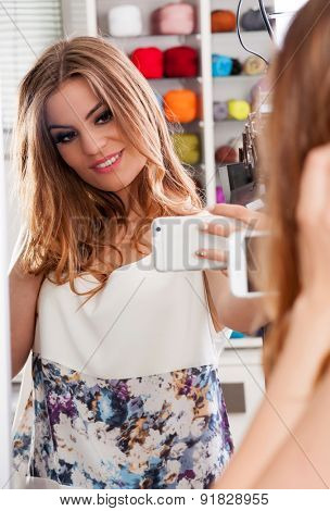 Beautiful teenage girl taking selfie in a mirror