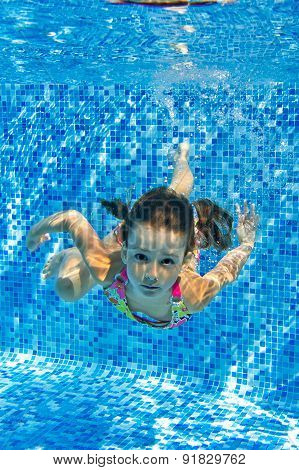 Happy smiling underwater child in swimming pool, beautiful healthy girl swims and having fun