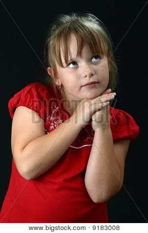 Small girl resting chin on her hands looking up on black