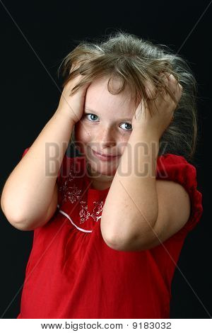 Small girl with hands in her hair looking at camera on black
