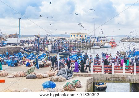 AS-SAWIRA, MOROCCO, APRIL 7, 2015:  Local people and tourists walk in busy fishing port of As-Sawira