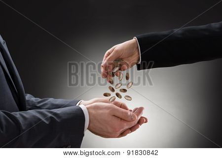 Businessman Pouring Coins On Colleague's Hand