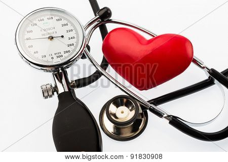 a sphygmomanometer, a heart and stethoscope lying on a white ground