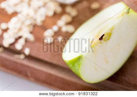 diet, vegetable food, cooking and objects concept - close up of green apple on wooden cutting board