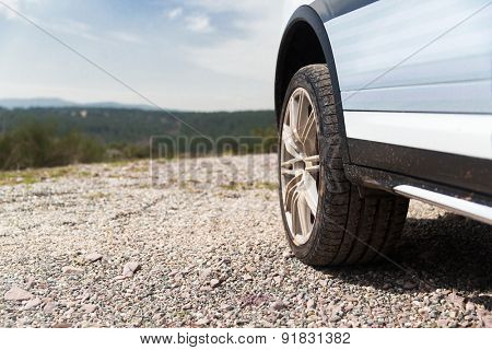 transport, driving and motor vehicle concept - close up of dirty car wheel on cliff