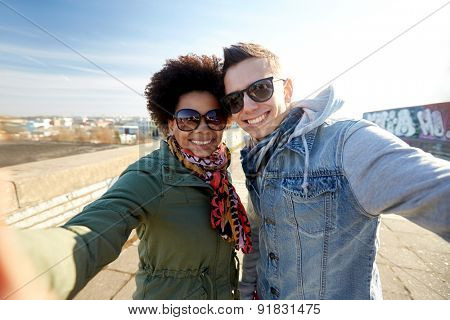 tourism, travel, people, leisure and technology concept - happy teenage international couple taking selfie on city street
