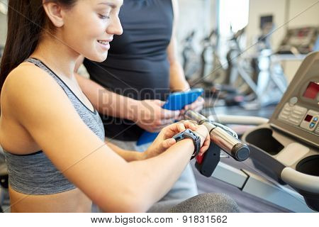 sport, fitness, lifestyle, technology and people concept - close up of woman setting heart-rate watch at gym with trainer