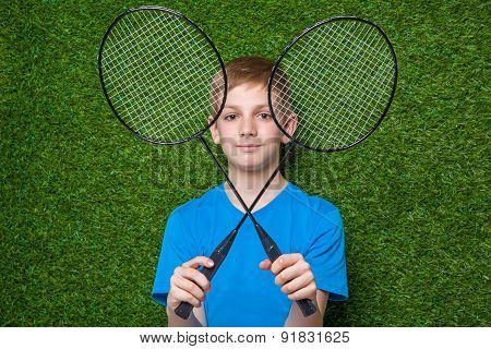 Happy boy holding badminton rackets over grass
