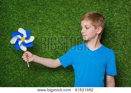 Boy looking at pinwheel over grass