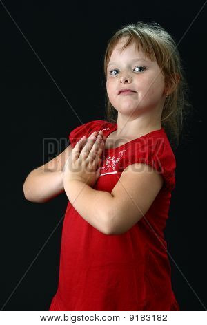 Small girl with clasped hands praying on black