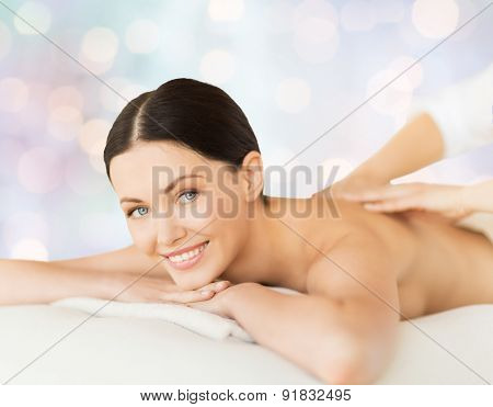 people, beauty, spa, holidays and body care concept - happy beautiful woman having back massage over blue lights background