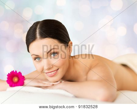 people, beauty, holidays and body care concept - happy beautiful woman lying on massage desk at spa over blue lights background