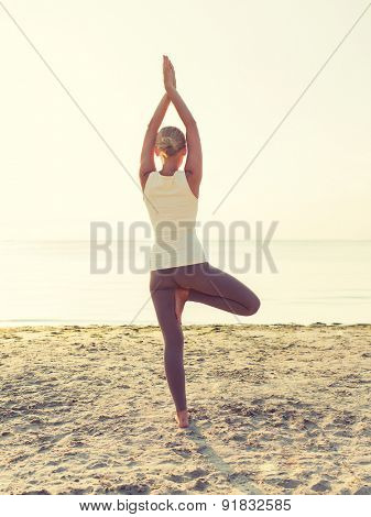 fitness, sport, people and lifestyle concept - woman making yoga exercises on sand outdoors from back