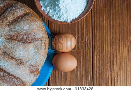Baking cake in rural kitchen - dough recipe ingredients eggs, flour and freshly bread on vintage woo
