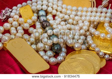 gold in coins and bars with decorations on red velvet. symbolic photo for wealth, luxury, wealth tax.