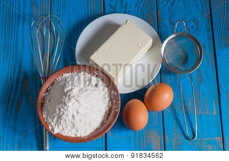 Baking cake in rural kitchen - dough recipe ingredients eggs, flour, butter and whisk, screen on vin
