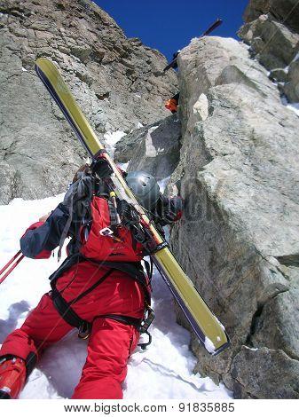 Tour skier climbing a rock