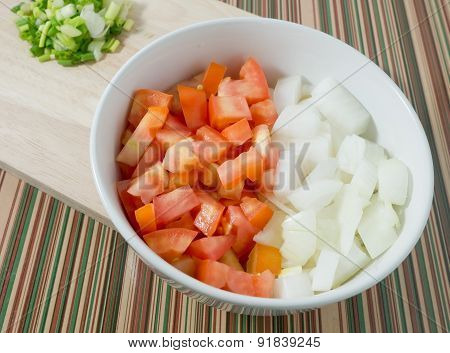 Chopped Tomatoes, Onions And Spring Onions On Cutting Board