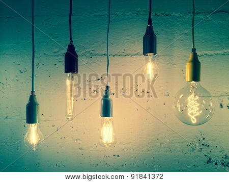 Illuminated Light Bulbs On Green Background