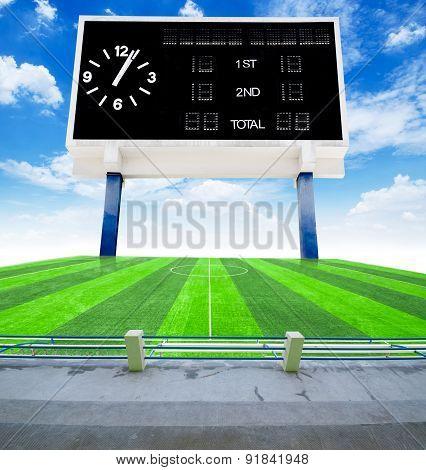Old Black Score Board In Field Soccer With Blue Sky.