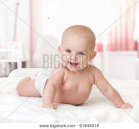 healthy happy baby lying on bed