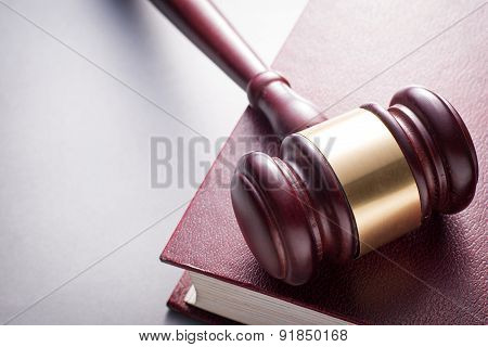 Wooden Gavel Resting On Red Leather Book