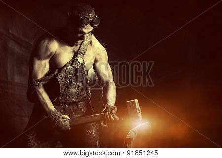 Rage muscular coal miner working with a hammer over dark grunge background. Smithy. Mining industry. Art concept.