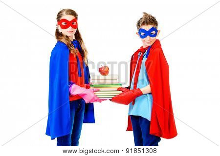 Boy and girl teenagers in a costume of superheroes holding books together. Isolated over white background.