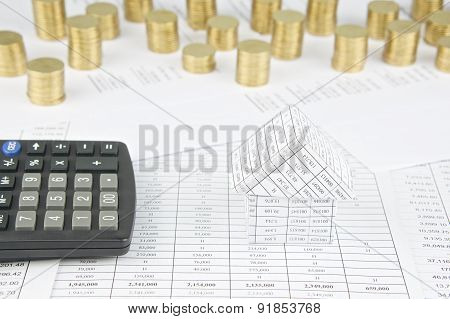 House With Calculator Have Pile Of Gold Coins As Background