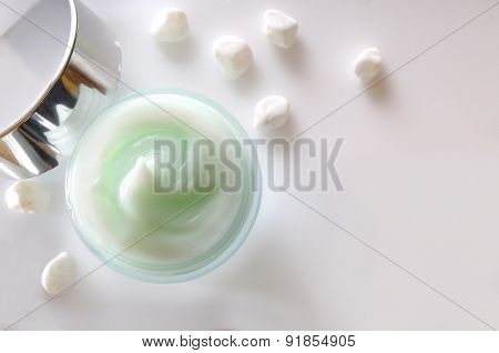 Cream Jar Open And Small White Stones Isolated Top View