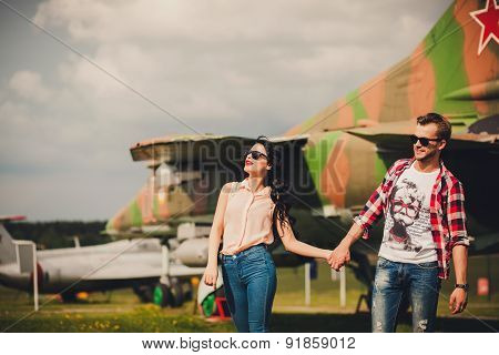 Fun And Stylish Couple Walking Near The Aircraft