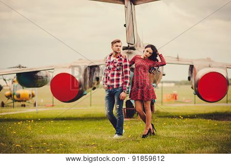 Stylish Couple Standing Near A Plane
