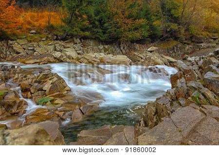 Rapids On A Rocky Mountain River In Autumn