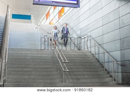 Full length of businessman and businesswoman walk down stairs at railway station