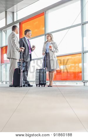 Full length of businesspeople talking on railroad platform
