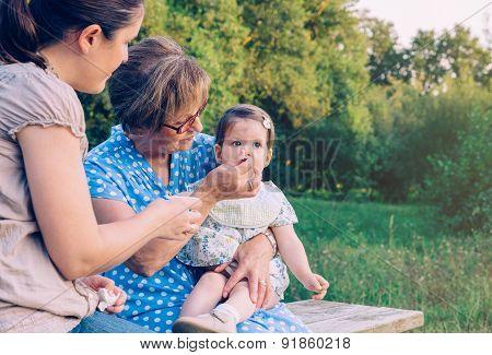 Senior woman feeding to baby girl sitting in a bench