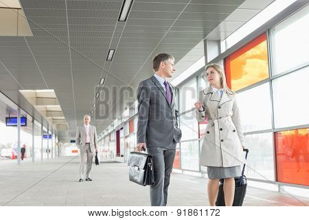 Businessman and businesswoman conversing while walking in railroad station
