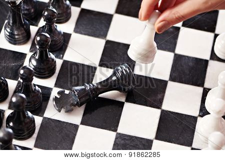 Hand With White Pawn Hits Black King