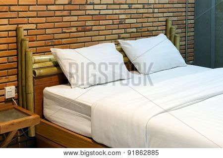 Empty bed with brown brick wall